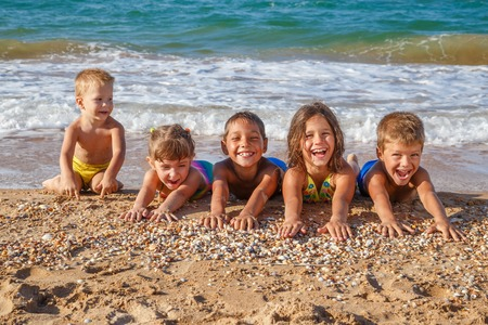 seashell: Five happy kids stretched out his arms on the beach