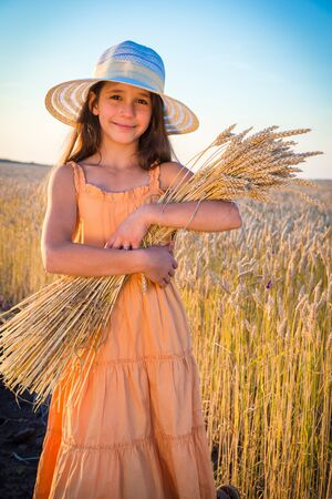 sheaf: Smiling girl with sheaf of wheat standing on the field Stock Photo