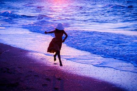 piedi nudi di bambine: Ragazza che funziona lungo il surf al tramonto