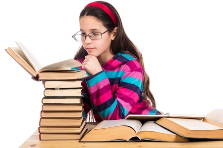 reading glass: Girl in glasses reading the old book with pile of books, isolated on white Stock Photo