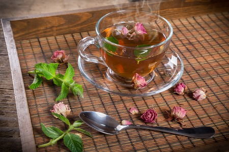 leaves green: Cup of green tea with mint and dried rose buds on old wooden tray Stock Photo