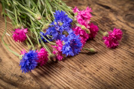 bluet: bouquet of blue and red cornflowers on wooden background