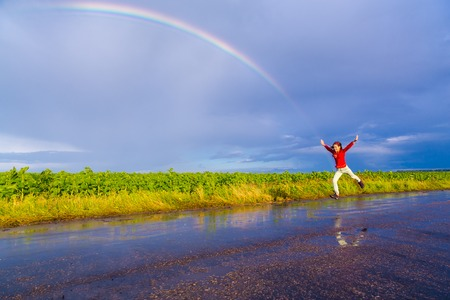 Happy girl jumping on wet road with rainbow after rain, with copy-space