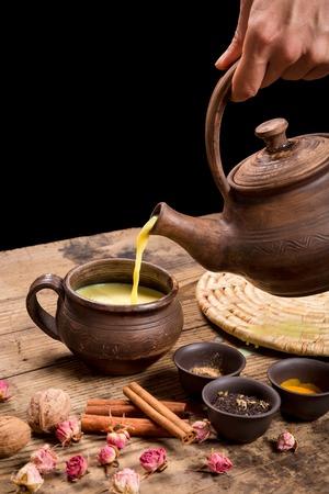 Pouring masala tea from dark ceramic pot Stockfoto