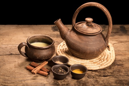 chai: Masala tea with spices on dark wooden table Stock Photo