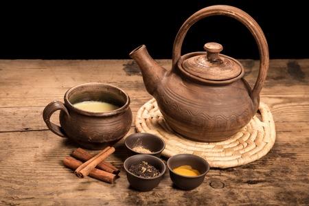 yerbas: Té Masala con especias en la mesa de madera oscura Foto de archivo