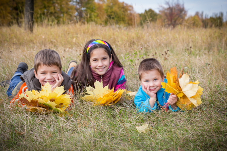 lying on leaves: Three smiling kids with yellow autumn leaves lying on withered grass in park