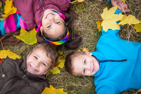 Three happy kids lying together on withered grass with fallen leaves, outdoors