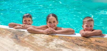 pool side: Three kids relaxing on swimming pool, summer concept Stock Photo