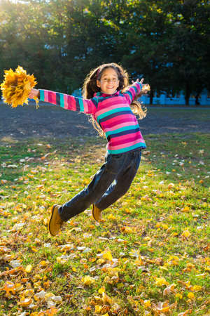 beautiful teen: Jumping girl with autumn leaves in park Stock Photo