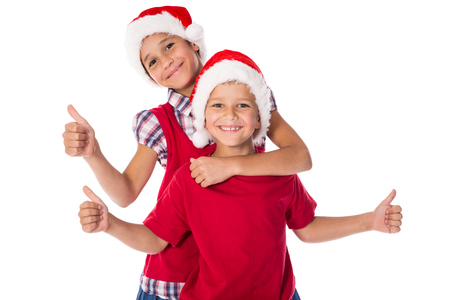 Two happy kids in Christmas hats together with thumbs up sign, isolated on white