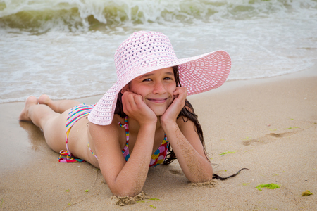 Happy girl in hat on the beach lying down on the sand near water Stock Photo