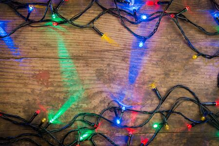 harsh light: LED Christmas lights on wooden background, abstract template Stock Photo