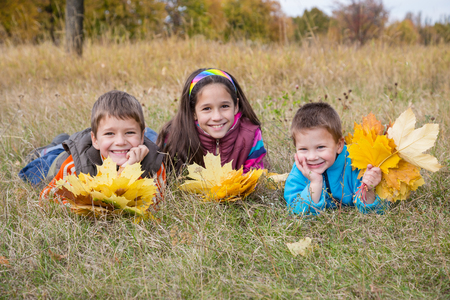 kids outside: Three smiling kids with yellow autumn leaves lying on withered grass in park