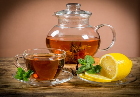 old desk: Cup and teapot of green tea with lemon and mint on old wooden desk Stock Photo
