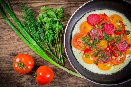 tomato slices: Fried eggs with greens, sausage and tomato slices on pan, wooden background