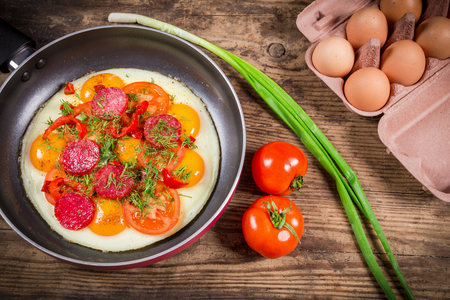 tomato slices: Fried eggs with greens, raw eggs, sausage and tomato slices on pan, wooden background Stock Photo