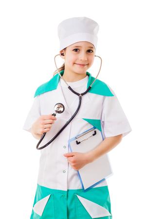 fonendoscopio: Ni�a en un traje de m�dico con estetoscopio en la mano, aislados en blanco