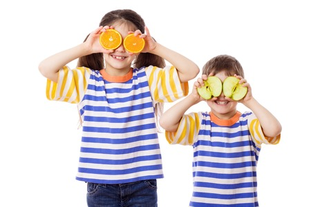 citrus family: Two funny kids with sliced fruits on face, isolated on white