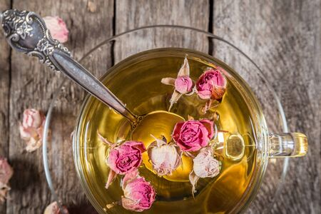 Closeup of green tea cup with teaspoon and dried rose buds on old wooden table, above view