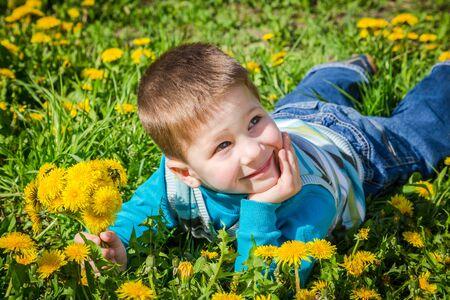 Ragazzino felice con il mazzo di denti di leone sdraiato sul campo verde