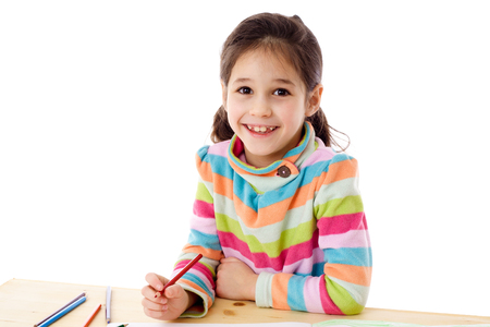 Smiling little girl at the table draw with crayons, isolated on white Stock Photo