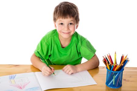 zeichnen: Inspiriert kleiner Junge am Tisch mit Bleistiften zu zeichnen, isoliert auf weiß