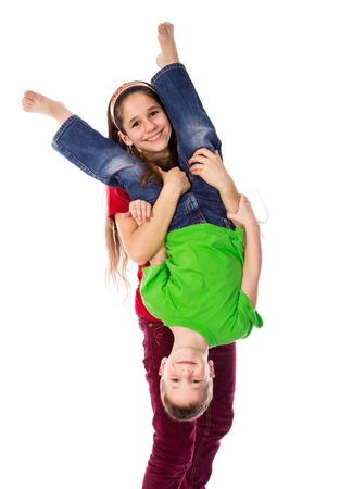 girl care: Two kids playing together, girl holding his brother upside down, isolated on white