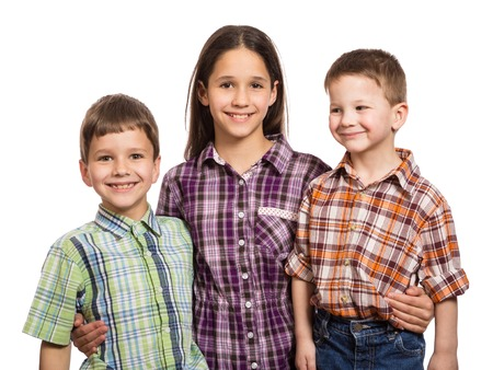 young boy smiling: Family with three happy kids standing together, isolated on white