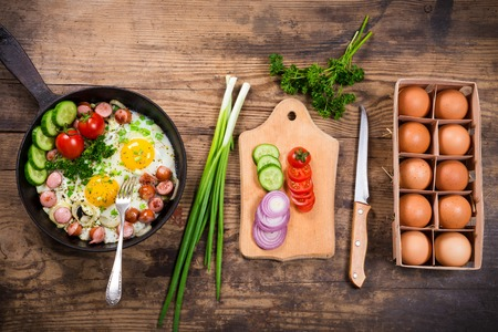 Morning cooking with fried eggs, sausages and vegetables in pan on old wooden table Stockfoto