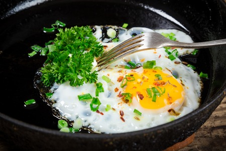 rustic food: fried egg with greens in pan on old wooden table, closeup Stock Photo
