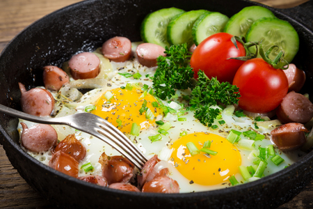 rustic food: Tasty breakfast - two fried eggs with sausages in pan