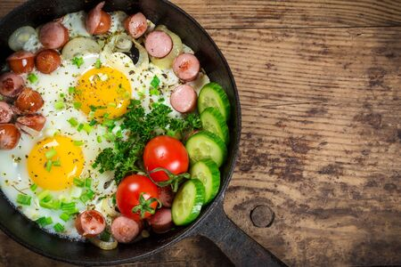 rustic food: two fried eggs with sausages in pan on old wooden table, space for text