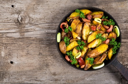 Irish sliced fried potatoes with sausages in pan on old wooden table, space for text Stock Photo