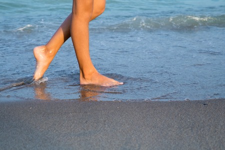 jolie pieds: Belles jeunes jambes de femme sur la plage au coucher du soleil