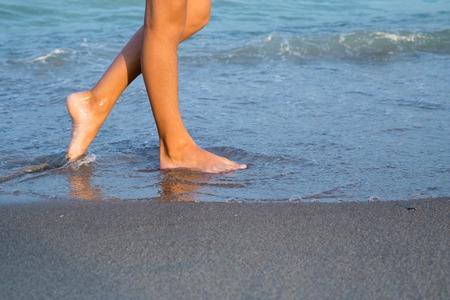 Schöne junge Frau, die Beine am Strand bei Sonnenuntergang Standard-Bild