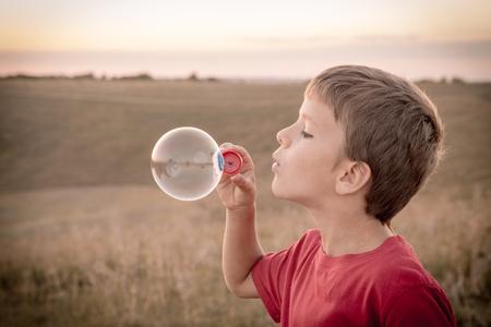soap: boy blowing up the soap bubbles on sepia toned landscape