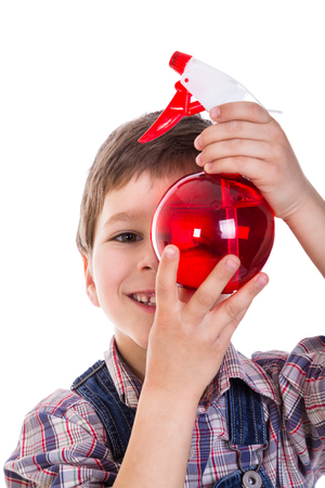 humidify: Smiling boy with red sprayer in hands, isolated on white
