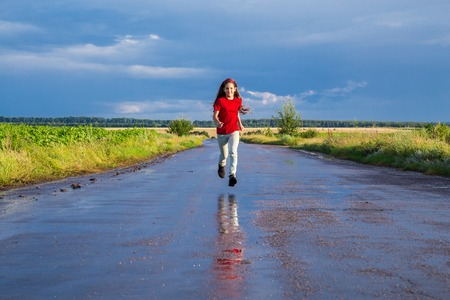 rain wet: Happy girl running on wet road after rain