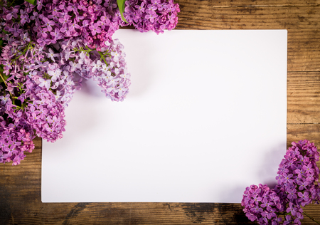 Bunch of lilac on brown wood old table with blank paper page, empty space for text Stockfoto