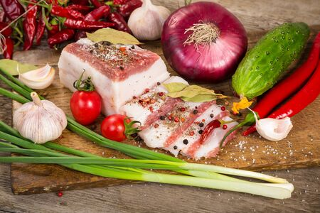 lard: salted lard with spices and vegetables on woden cutting board