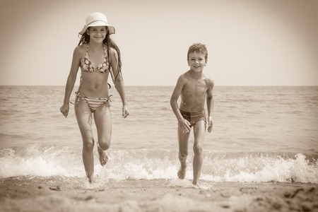 run out: Two happy kids on the beach run out from the sea, sepia toned picture Stock Photo