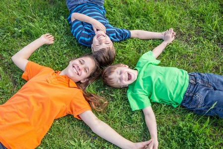 boys playing: Three smiling kids lying down together on green grass meadow