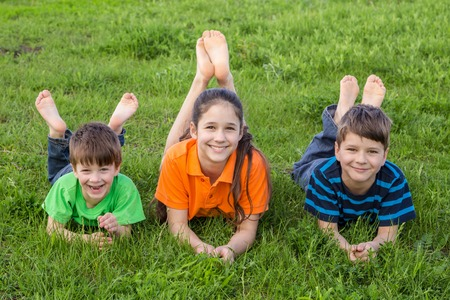 young girl barefoot: Three smiling kids lying together on spring green grass meadow