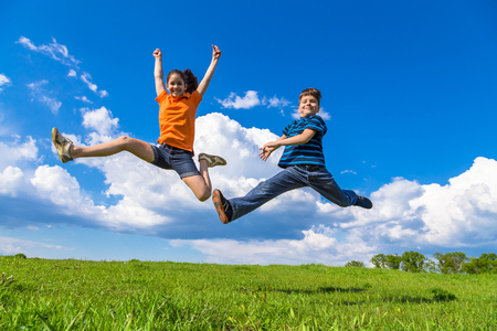 spring landscape: Happy kids jumping on green hills against blue sky