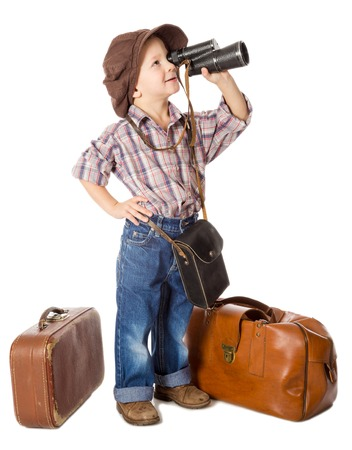 far away look: Traveling little boy with old suitcases looking to spyglass, isolated on white Stock Photo