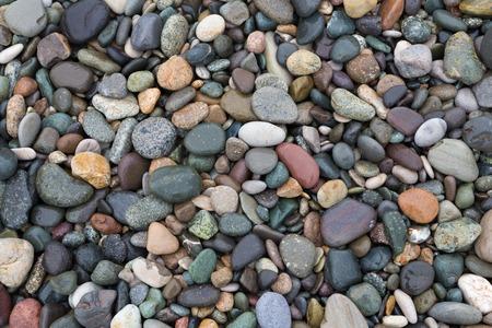 Gros plan de cailloux humides colorés sur la plage, fond naturel.