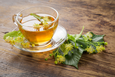 lime blossom: Herbal tea with linden flowers on old wooden table