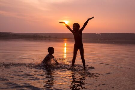 Silhouette of two boys jumping into water on sunset