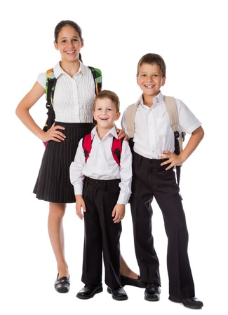 schoolgirl uniform: Three happy students with rucksacks standing together, isolated on white Stock Photo